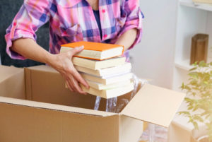 a closeup of a person packing a box full of books