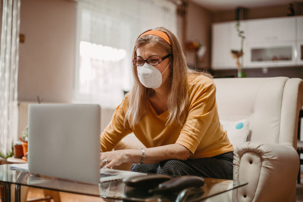 senior woman uses her computer with face mask