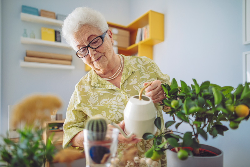 Elderly woman watering her plants inside her senior living community