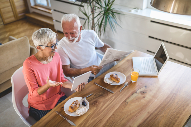 senior couple eats breakfast and uses laptop
