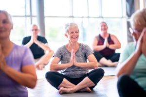 a group of seniors taking a yoga class at their senior living community