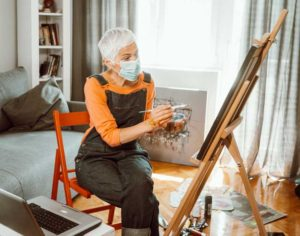 a senior woman painting in her senior apartment