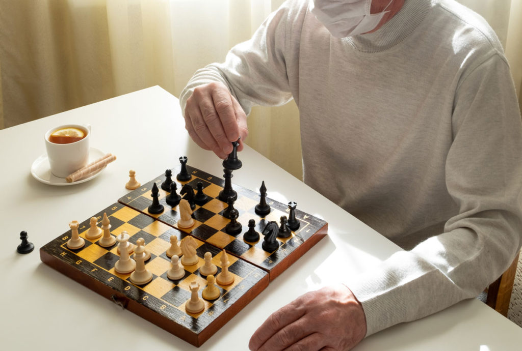 senior man plays chess with a face mask on