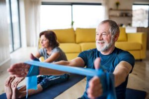an elderly couple practicing yoga in their senior apartment