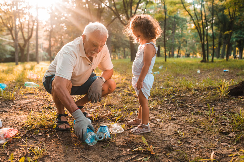 a grandpa picking up trash with his granddaughter