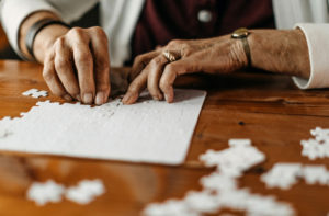 a closeup of a pair of hands working on a jigsaw puzzle