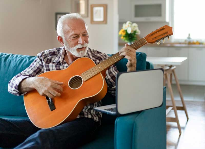 senior man playing a guitar