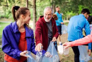 a senior man volunteering and picking up trash
