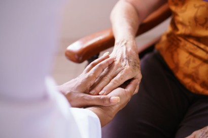 senior touching hands with another in a retirement home