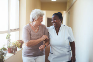 a senior woman walking around her senior living community with her caregiver