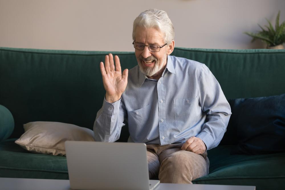 Senior man waving while on a video call