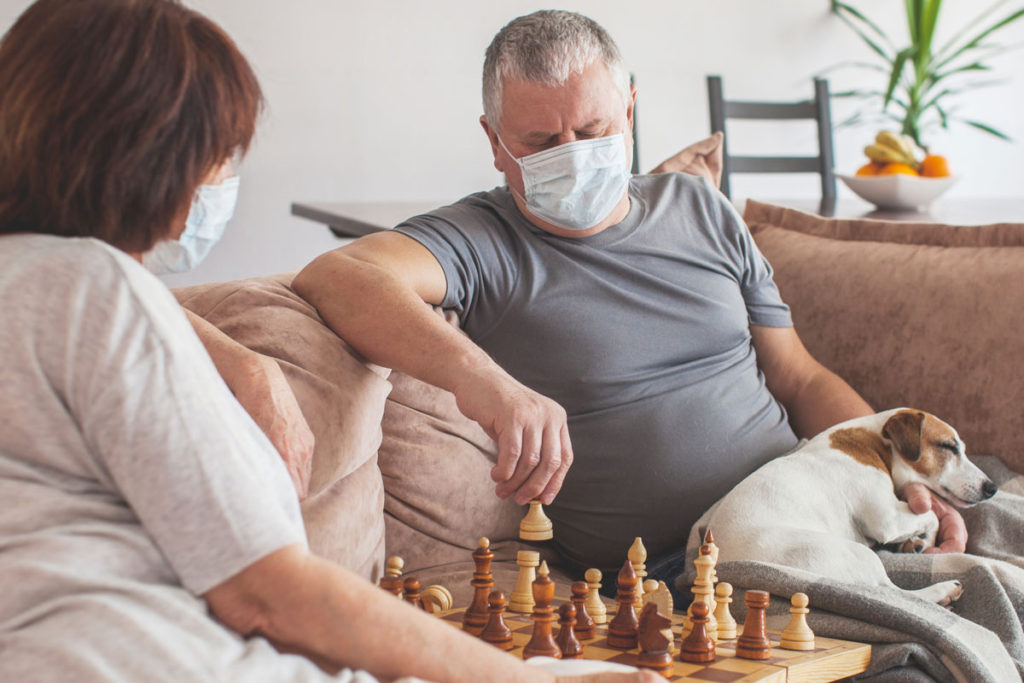 two seniors play chess against each other with dog on their lap
