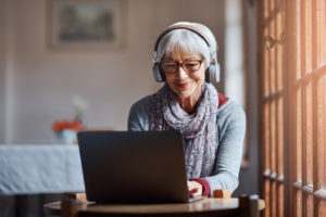senior woman with headphones types on her laptop
