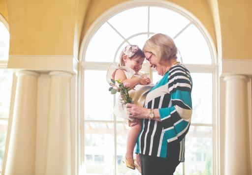 Senior woman holding her granddaughter in her senior apartment