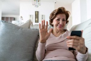 a senior woman talking to a loved one using video chat