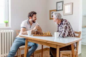 a senior man talking and playing chess with his adult son