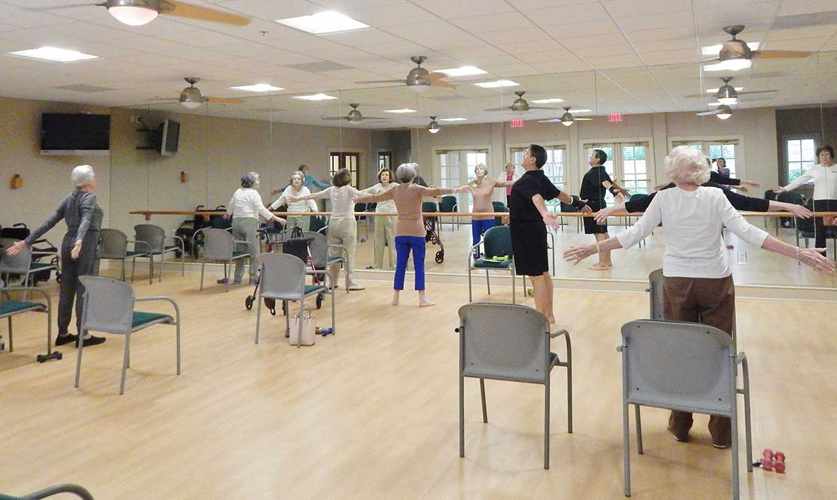 A group of Edgemere residents taking a yoga class in the community's fitness center