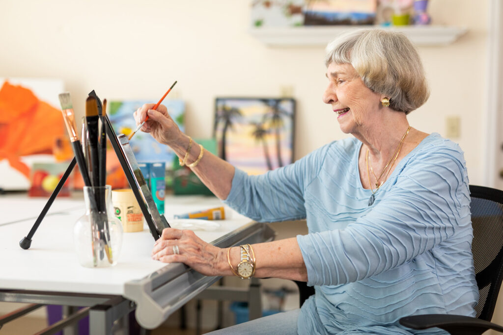 senior resident taking time to enjoy painting a picture