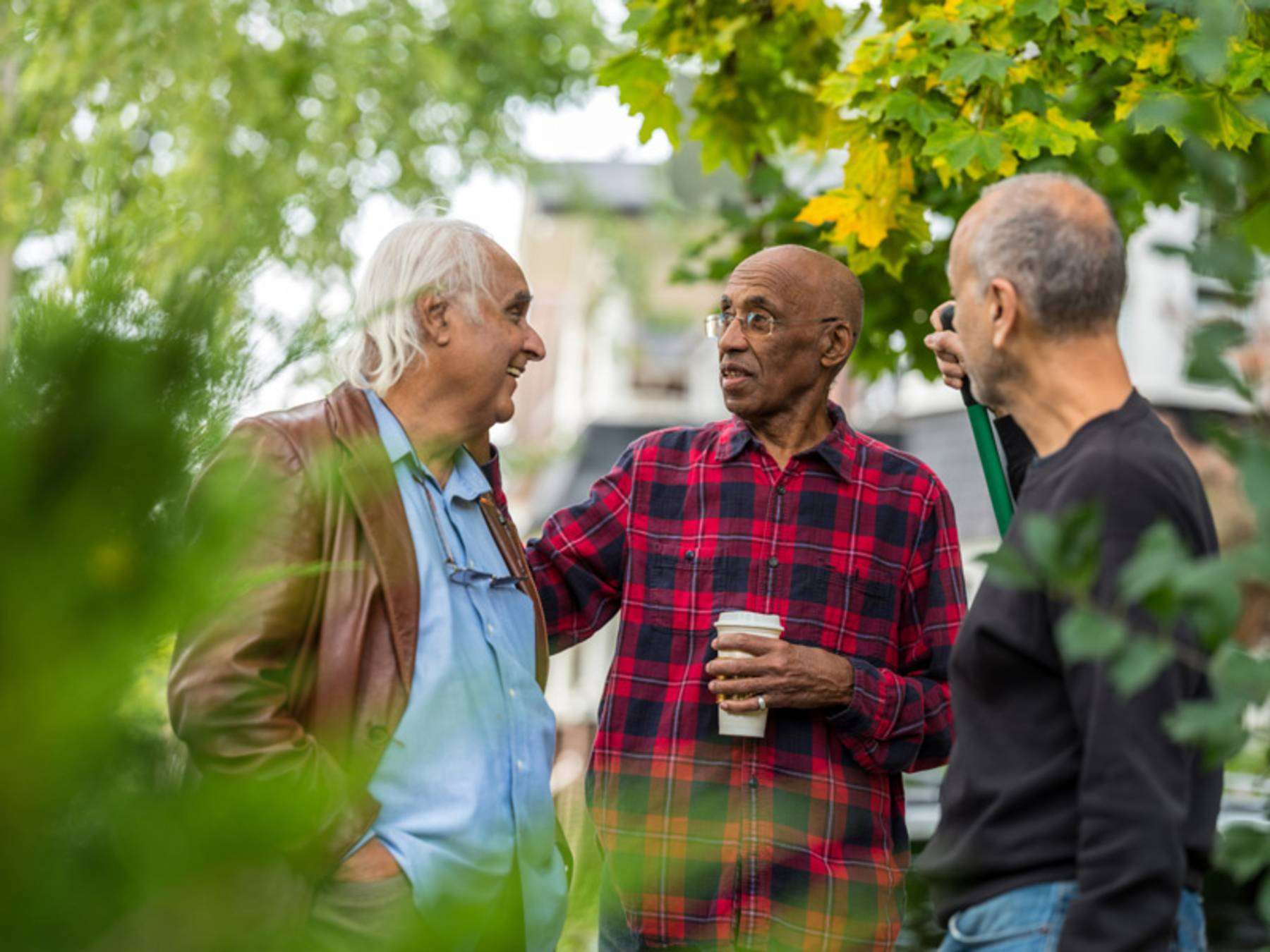 A group of senior men talk while standing outdoors