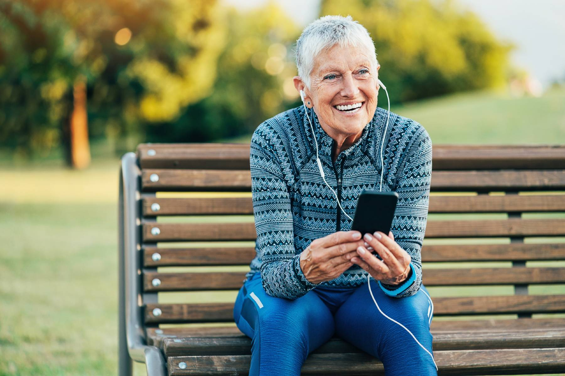 A senior woman in athletic gear stops her run and sits on a park bench to list to music on her phone