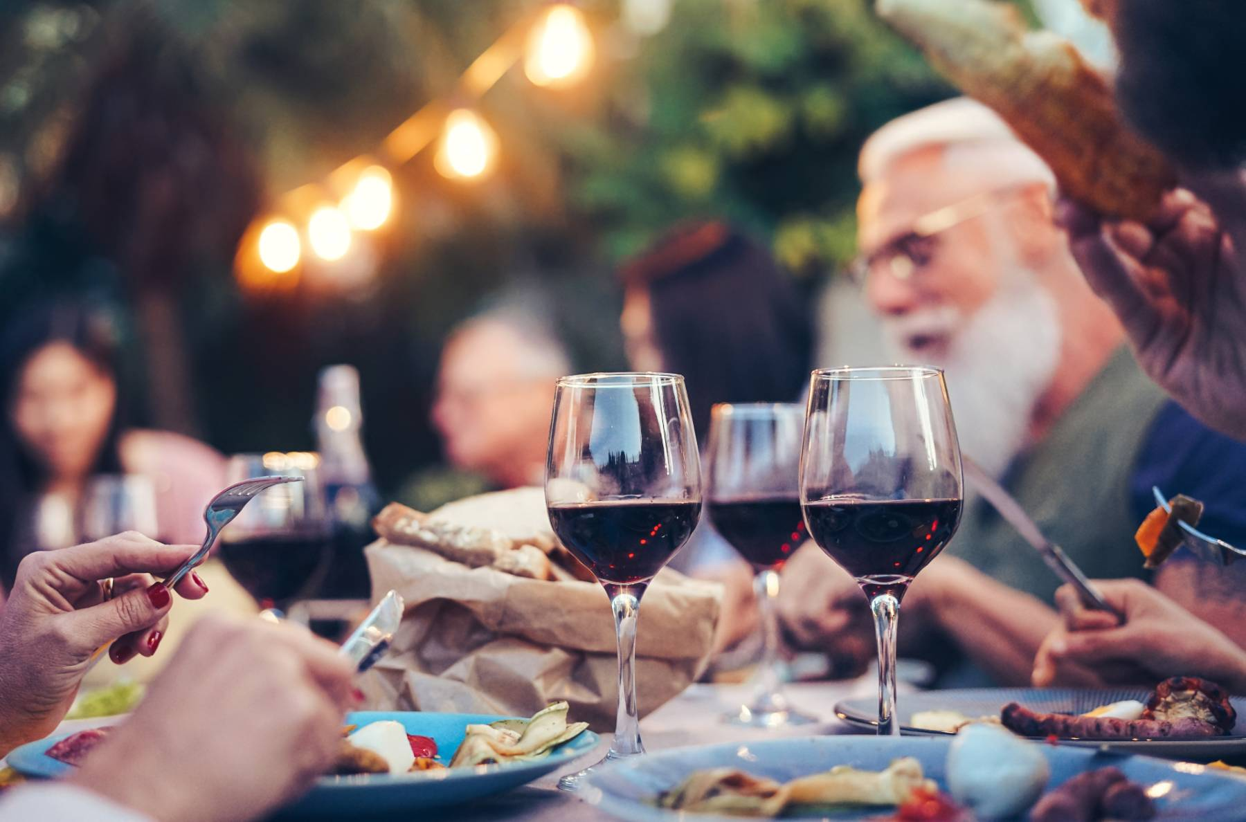 A group of people eat outside under string lights and drink red wine and eat a meal together