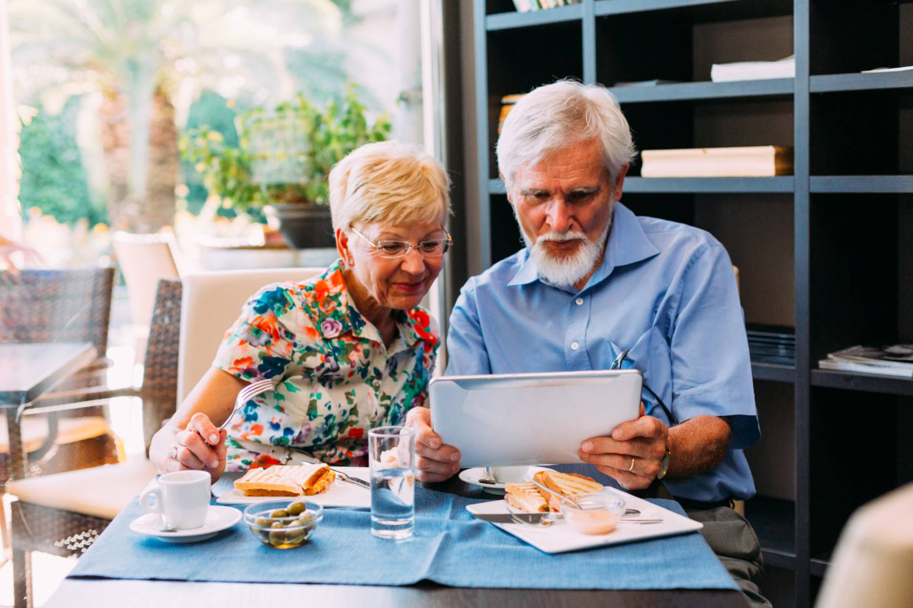 A senior couple enjoy breakfast and look at an ipad or tablet together
