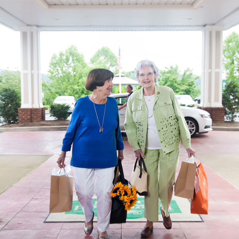 two women walking into a senior living community