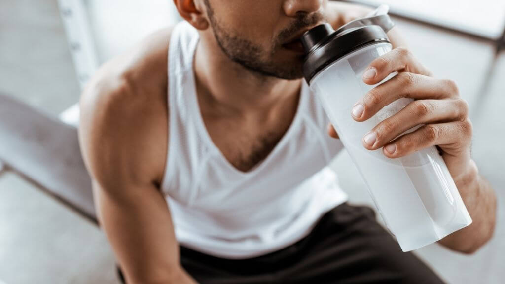 Young man drinking a pre-workout mix