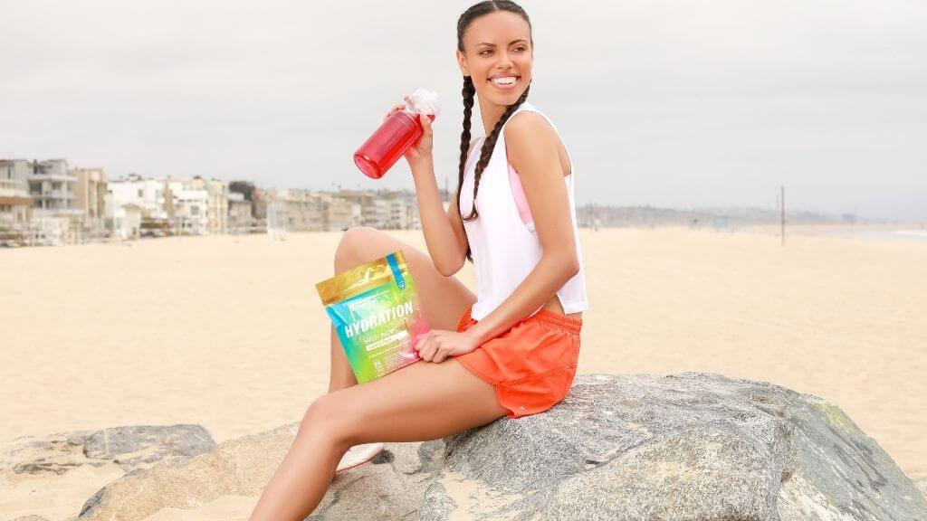 Essential elements Hydration Variety pack with a woman at the beach
