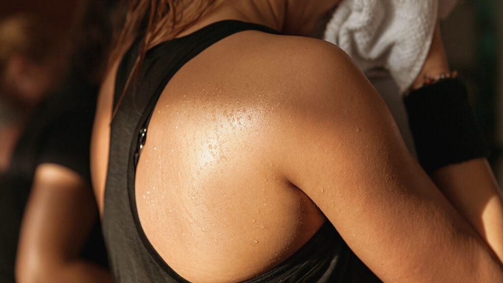 Close-up shot of the sweat on a woman's shoulder at the gym