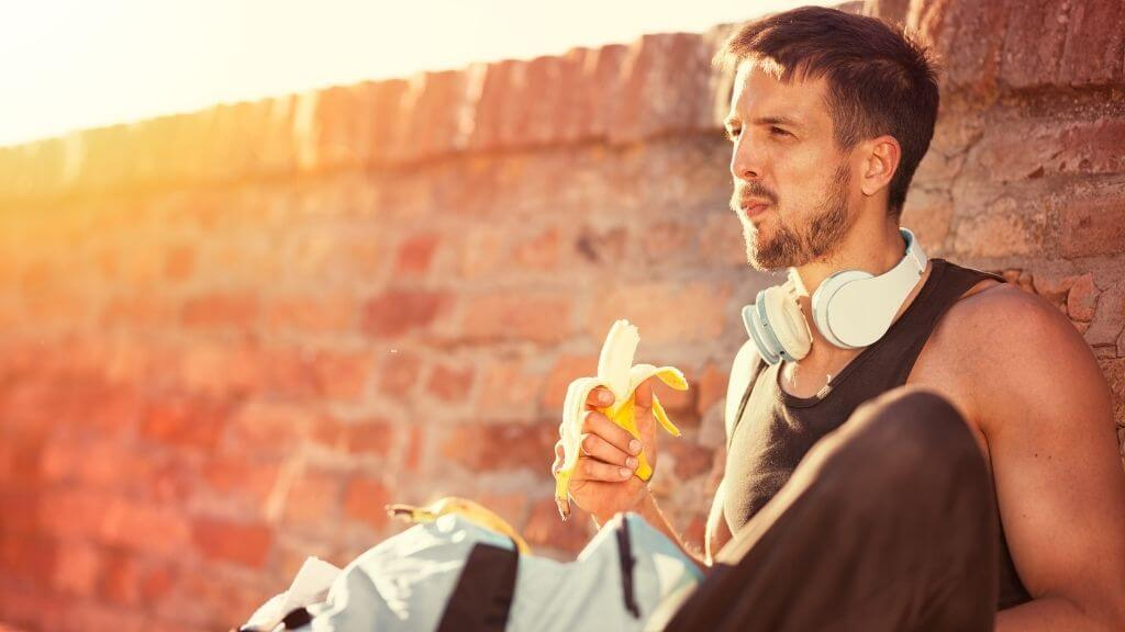 Young man having a banana before work out