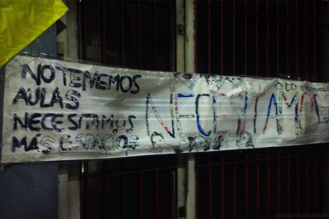 En la fachada del edificio se pueden leer carteles con la postura de alumnos, padres y docentes.