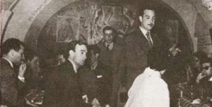 Tomás Cruz, de pie y con bigote, en una de las tertulias literarias del local Cuevas de Sésamo en Madrid. / Blog amanecenublado