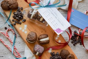 Holiday cookies in a gift bag, candy cane, and other ingredients on a cutting board