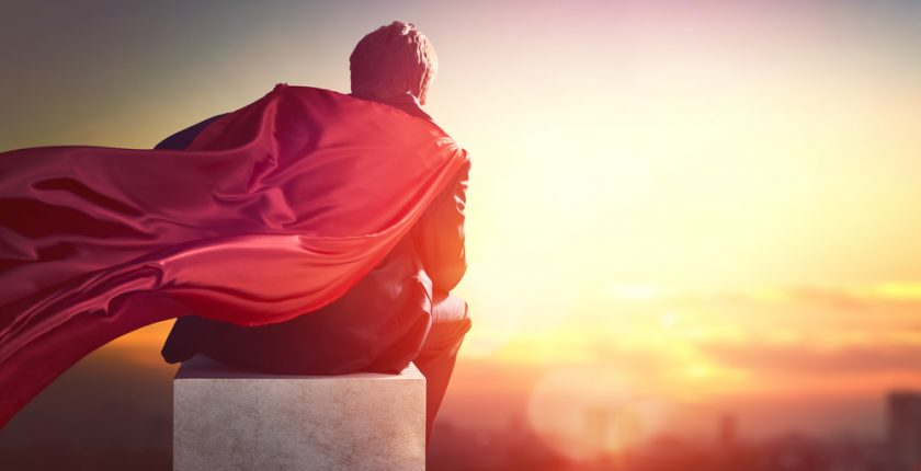 Man sitting, wearing a cape and facing sunset