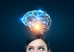 Close up of a black haired woman s head looking to the left and standing near a dark blue wall with a blue brain hologram shining with an orange light above her head