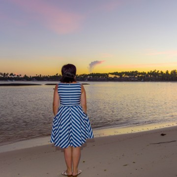 A middle-aged single mom on vacation without her kids, watching the sun rise over the sea—ESME.com