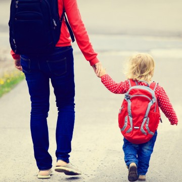 Mother holding hand of little daughter with backpack going to school—ESME.com