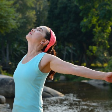 Greiving, healing widow stretching her arms to enjoy the fresh air in the park—ESME.com