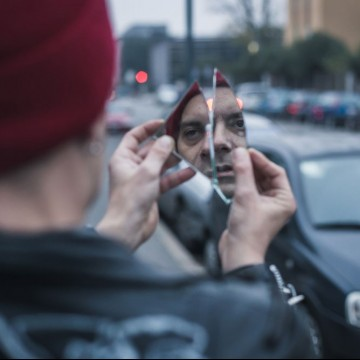 Punk guy looking at himself in a shattered mirror in the city streets- ESME.com