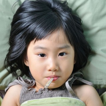 A sick girl in bed with a thermometer in her mouth - ESME.com
