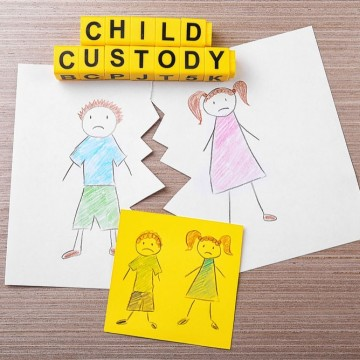 """Torn drawing on wooden table with words """"child custody,"""" illustrating what single moms should expect during a custody battle—ESME.com"""