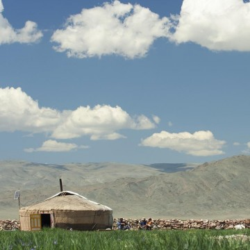 A Mongolian yurt with inhabitants in front of it, summertime—ESME.com