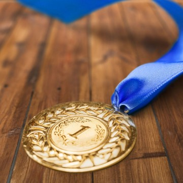 A first-place medal on a wood floor—ESME.com