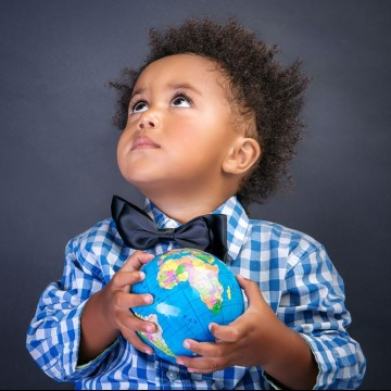 Portrait of cute little adopted boy holding a small globe—ESME.com