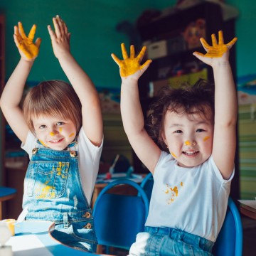 Little friends paint a picture and are covered in paint, symbolizing that single moms and their kids should get creative—ESME.com