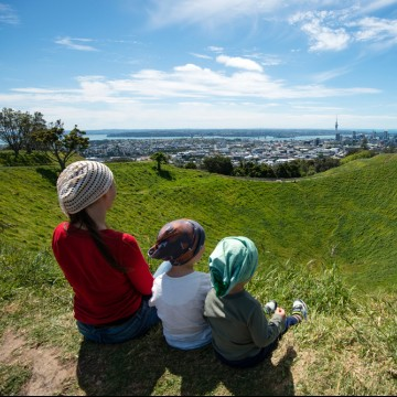 Single mom with two kids enjoying the view of Auckland skyline from Mount Eden—ESME.com