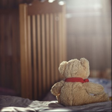 Teddy bear in an empty child's room, symbolizing the emotional pain of having an early miscarriage as a single mom—ESME.com