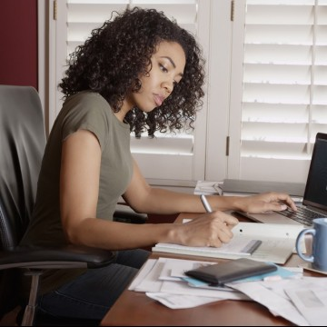 Woman working on paperwork at her desk—ESME.com