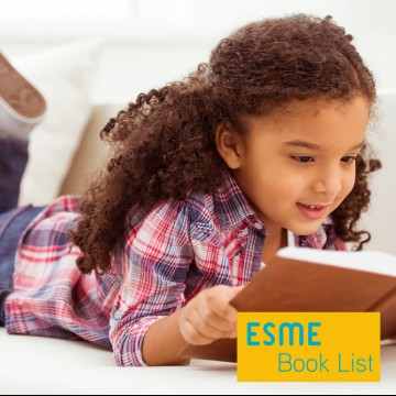 Cute little girl in casual clothes reading a children's book about adoption and smiling while lying on a sofa in the room—ESME.com